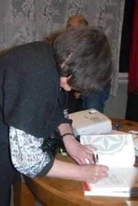 Tosia podpisuje książkę swojego autorstwa.