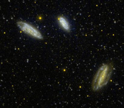 Szerokokątny obraz w ultrafiolecie oddziałujących ze sobą galaktyk NGC 7582 (w prawym dolnym rogu zdjęcia, por. tekst), NGC 7599 i NGC 7590.