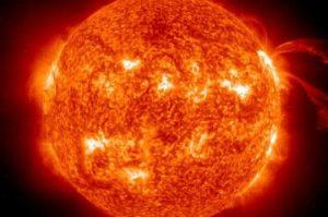 Słońce, protuberancje (strumienie nad powierzchnią) i regiony silnego pola magnetycznego (na biało).