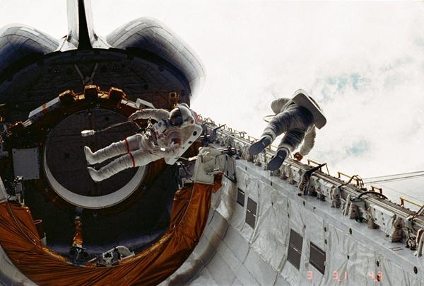 """Spacer dwóch astronautów w pobliżu luku bagażowego """"Challengera"""". Donald Peterson po prawej."""